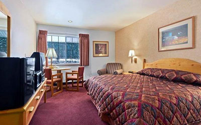 King bed hotel room with burgundy decor